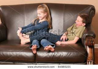 Cute Little Girl Tickling BrotherS Feet Stock Photo 84965221